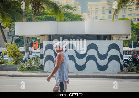 RIO DE JANEIRO, BRAZIL - MARCH 06, 2016: Man walking into wall with sidewalk mosaic of Copacabana Beach, Rio De - Stock Photo