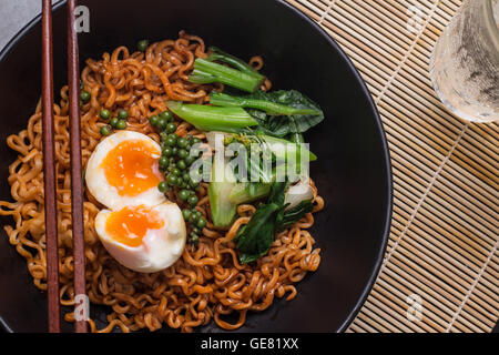 noodles in black bowl garnished on kitchen table - Stock Photo