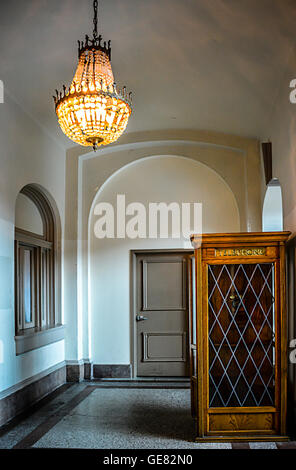 Chandelier and vintage wooden pay telephone booth in moody Beaux Arts interior of the Chattanooga Choo Choo Hotel - Stock Photo