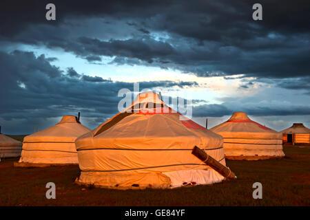 Gers or yurts of the Khatan Ugii Tourist Camp at sunset at Lake Ogii Nuur, Mongolia - Stock Photo