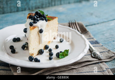 Cottage cheese baked pudding, sour cream and blueberries in a rustic style - Stock Photo