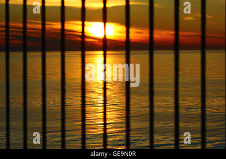 The sunset in the evening at the Baltic sea behind the bars - Stock Photo