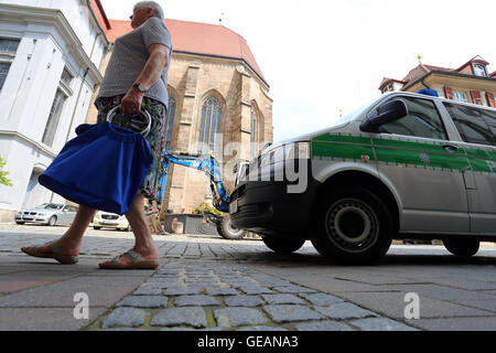 Ansbach, Germany 25th July, 2016 Ansbach, Germany. 25th July, 2016. A woman walks past a police vehicle near the - Stock Photo