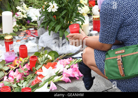 Munich, Germany. 25th July, 2016. A woman holds a memorial candle as she kneels next to flowers and candles that - Stock Photo