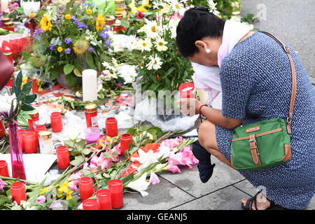Munich, Germany. 25th July, 2016. A crying woman holds a memorial candle as she kneels next to flowers and candles - Stock Photo