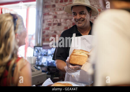 Shopkeeper in shop helping clients - Stock Photo
