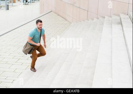 Young man walking upstairs - Stock Photo