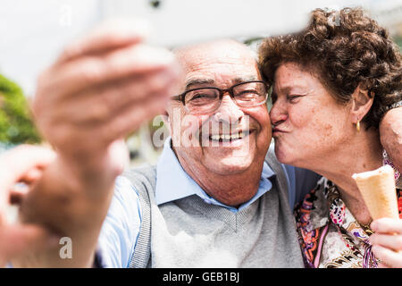 Portrait of smiling senior man taking selfie with his wife - Stock Photo