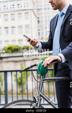 Businessman with bicycle walking in the city, using smart phone - Stock Photo
