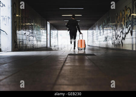 Businessman on business trip running with wheeled luggage - Stock Photo