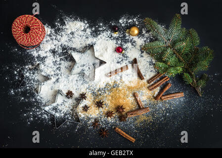 Cooking traditional Christmas holiday gingerbread cookies with cinnamon on black background - Stock Photo