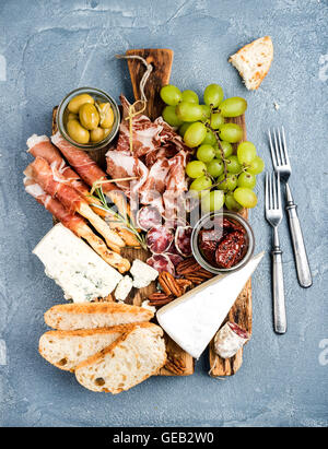Cheese and meat appetizer selection. Prosciutto di Parma, salami, bread sticks, baguette slices, olives, sun-dried - Stock Photo
