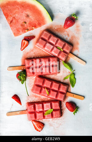 Strawberry watermelon ice cream popsicles with mint over steel tray background - Stock Photo