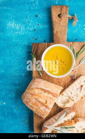 Mediterranean snacks set. Olive oil, herbs and sliced ciabatta bread on rustic wooden board - Stock Photo
