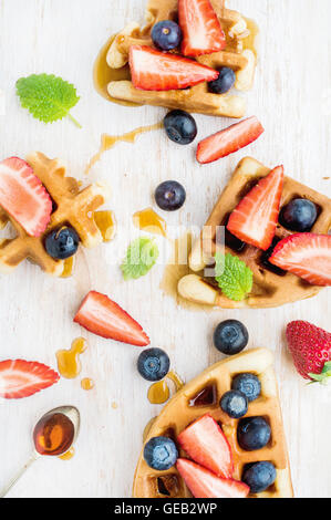 Home made Belgian waffles served on a white woodenl tray with berries , marple syrup and mint leaves - Stock Photo
