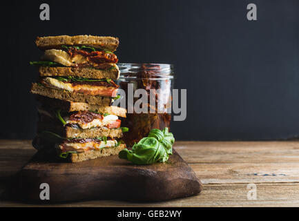 Caprese sandwich or panini. Whole grain bread, mozzarella, cherry and dried tomatoes, basil - Stock Photo