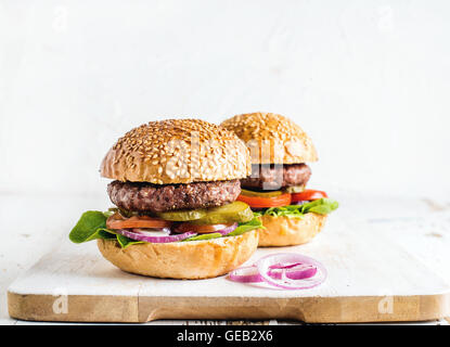 Fresh homemade burgers on wooden serving board with onion rings. - Stock Photo