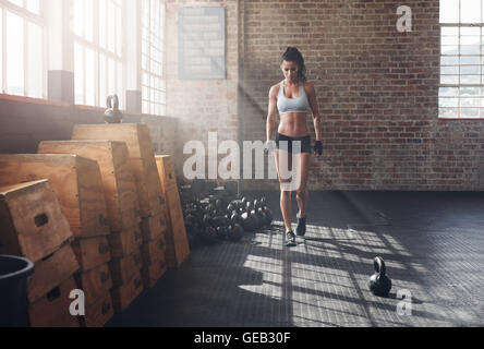 Full length shot of fitness woman walking in the gym with kettle bell on floor. Female athlete warming up before - Stock Photo