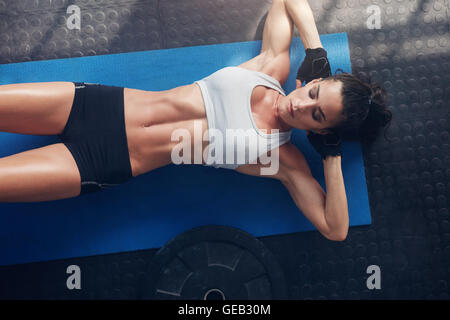 Top view of woman exercising on yoga mat. Fitness female lying on exercise mat with her hands behind head at gym. - Stock Photo