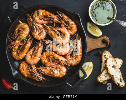 Roasted tiger prawns in iron grilling pan with fresh leek, lemon, bread and pesto sauce over black background - Stock Photo