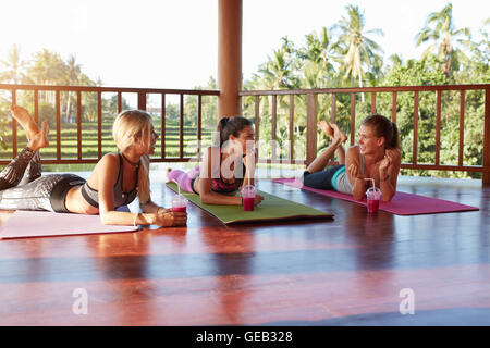 Three beautiful girls lying on the floor with fresh fruit juice and chatting after practicing yoga together. Group - Stock Photo