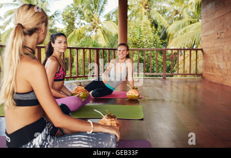 Women in yoga class taking break. Three beautiful girls relaxing with coconut juice and chatting after yoga session. - Stock Photo