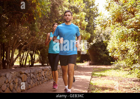 A guy and two girls running on a paved running trail with trees and a stone wall behind them wearing t-shirts and - Stock Photo