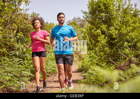 Three young joggers out for a run on a gravel path surrounded by bushes, wearing casual running clothes - Stock Photo