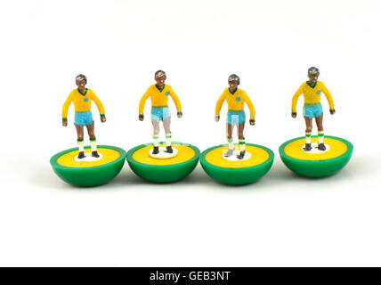 Four subbuteo soccer players forming a wall Brazil kit on white background - Stock Photo