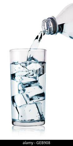 Water being poured into glass from bottle isolated on white background - Stock Photo