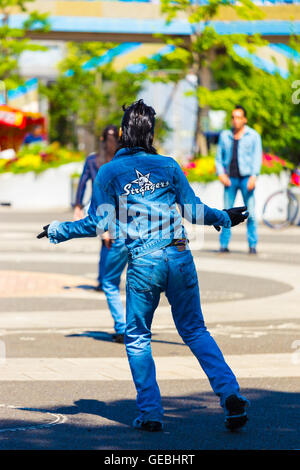 Rear of rockabilly dancing man in full jean outfit and slicked back hair performs to 50s rock and roll music weekly - Stock Photo