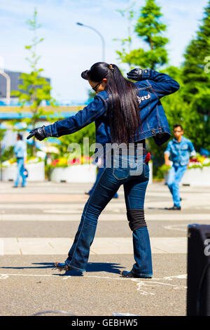 Rear of female rockabilly dancer in full jean outfit and vintage hairdo dancing to rock and roll music weekly at - Stock Photo