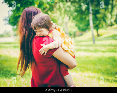 Mother holding her crying cute baby girl - Stock Photo