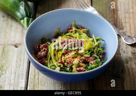 Courgette  spaghetti with sun dried tomatoes and mince hazelnuts - Stock Photo