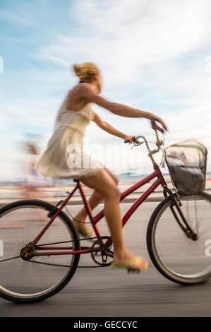 RIO DE JANEIRO - MARCH 6, 2016: A young Brazilian woman rides her bicycle in motion blur on the Ipanema Beach beachfront - Stock Photo