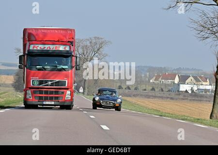 Jaguar E-type classic car overtaking a large red articulated lorry on a clear road in the French countryside in - Stock Photo