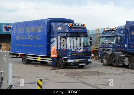 Driver in a truck cab talking to the yard man in a haulage firm yard - Stock Photo