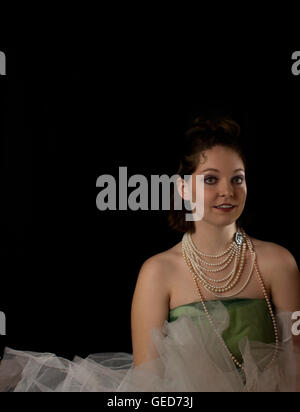 Beautiful woman wearing pearls, crinoline and green tulle on black background - Stock Photo