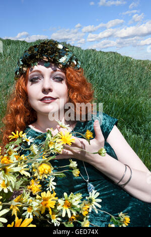 Beautiful young woman with long, curly red hair wearing green and holding yellow flowers. - Stock Photo