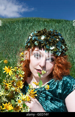 Beautiful young woman with long, curly red hair wearing green hat and dress and holding yellow flowers. - Stock Photo