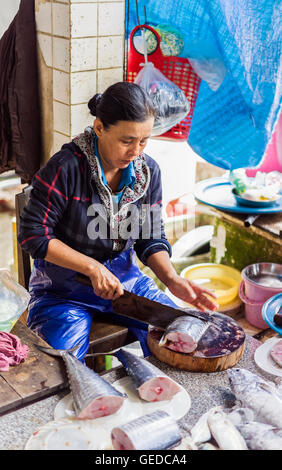 Hoi An, Vietnam - February 17, 2016: Asian woman cutting and selling fresh fish in the street market in Hoi An, - Stock Photo