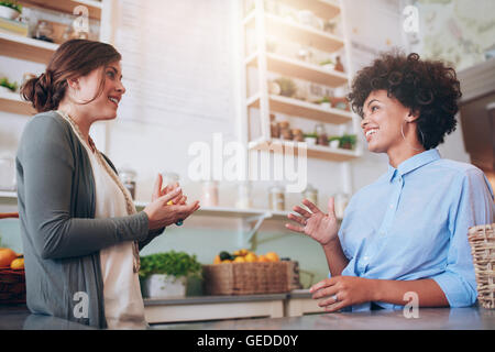 Two happy young female waitress standing behind a bar counter talking to each other. Juice bar partners discussing - Stock Photo