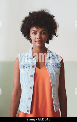 Portrait of beautiful young woman looking at camera confidently. African female model looking confident in smart - Stock Photo