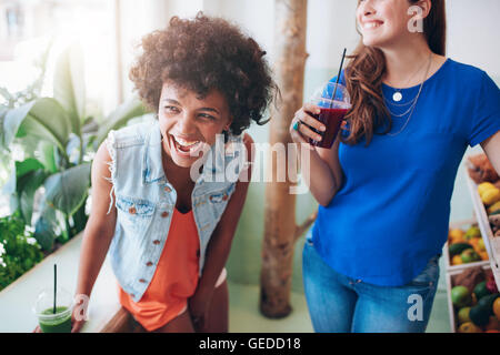 Portrait of cheerful young women at juice bar having a glass of fresh juice. Friends enjoying a juice bar. - Stock Photo