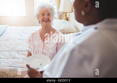Indoor shot of senior woman sitting on bed and home care nurse giving medication. Caucasian elderly woman smiling. - Stock Photo
