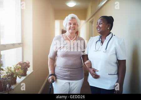 Happy healthcare worker and senior woman together at nursing home. Caring female doctor assisting a senior patient - Stock Photo