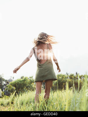 Rear view shot of a young woman in the field with sun flare. Beautiful female in sundress in a summer field. - Stock Photo