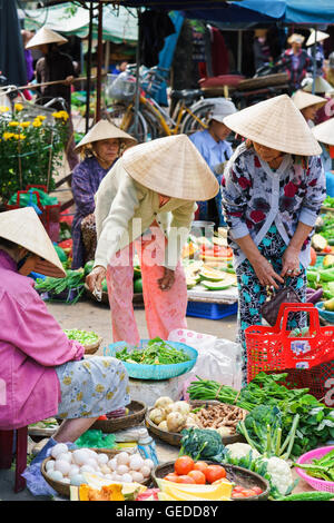 Hoi An, Vietnam - February 17, 2016: Asian traders selling fresh vegetables to customers in the street market in - Stock Photo
