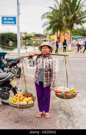 Hoi An, Vietnam - February 16, 2016: Asian seller carrying fresh fruit in bowls on her shoulders in the street in - Stock Photo