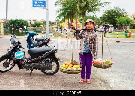 Hoi An, Vietnam - February 16, 2016: Asian woman greengrocer carrying fresh fruit in bowls on her shoulders in the - Stock Photo